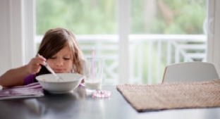Small child eating cereal at a table